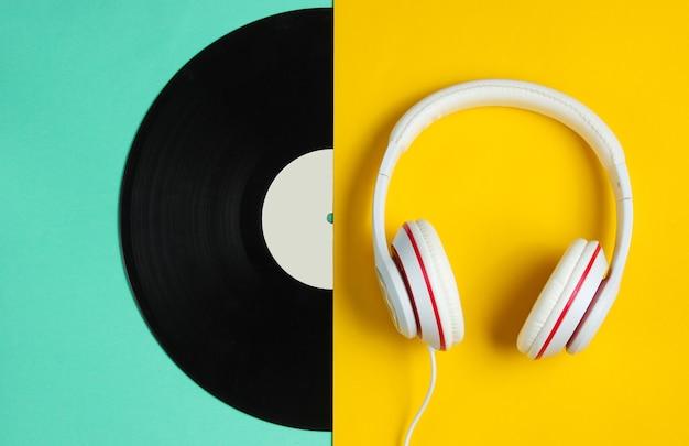 Conceito de música de estilo retro. fones de ouvido clássicos, meio disco de vinil em fundo de papel colorido. cultura pop.