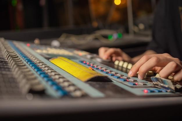 Conceito de música, tecnologia, pessoas e equipamento - homem no console de mixagem no estúdio de gravação de som sobre as luzes.