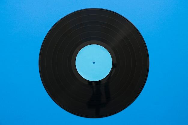 Conceito de música vintage com vinil no fundo azul