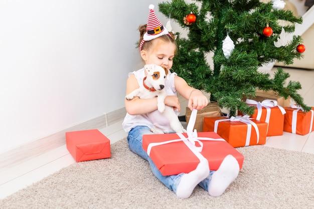Conceito de natal, animais de estimação e feriados - criança com chapéu de papai noel com um cachorro jack russell terrier