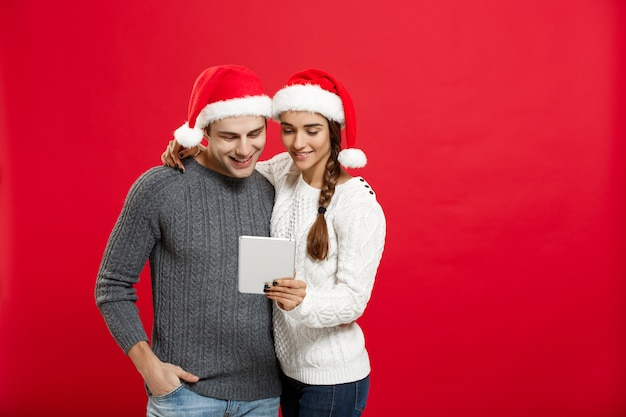 Conceito de natal - casal jovem e bonito gosta de jogar no tablet no dia de natal.