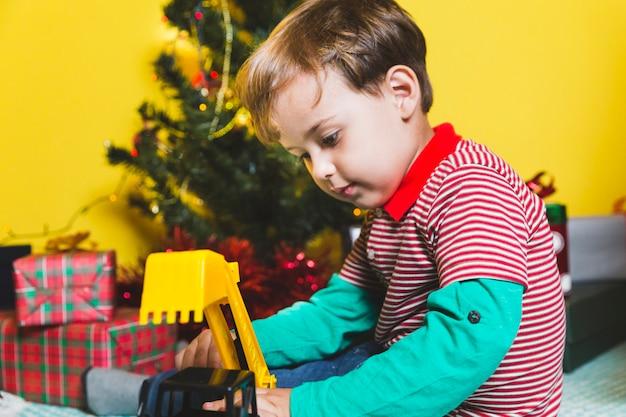 Conceito de natal com criança brincando na frente da árvore de natal