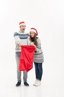Conceito de natal - comprimento total jovem casal atraente segurando um saco de papai noel isolado na parede cinza branca.