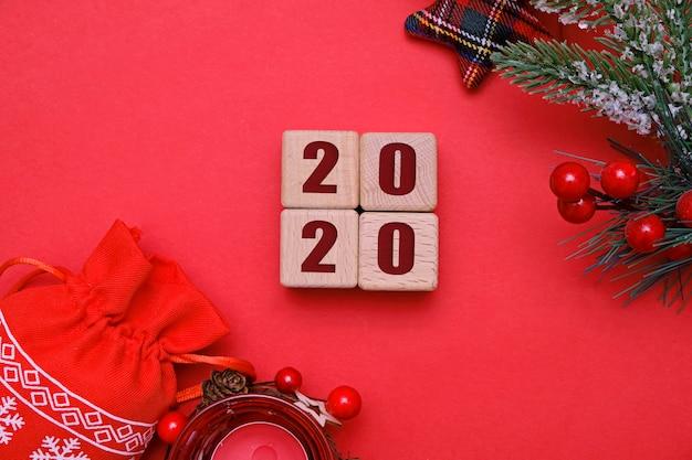 Conceito de natal e ano novo 2020, cubos de madeira e decorações em vermelho