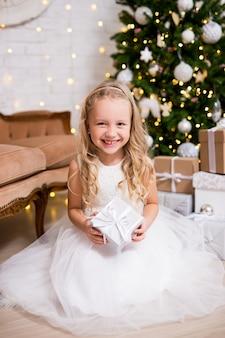 Conceito de natal e ano novo. menina bonita com vestido branco abrindo presentes de natal