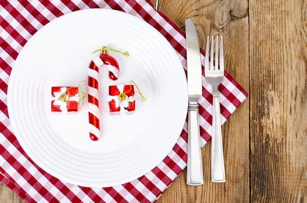 Conceito de natal e ano novo. prato branco, toalha de mesa vermelha.