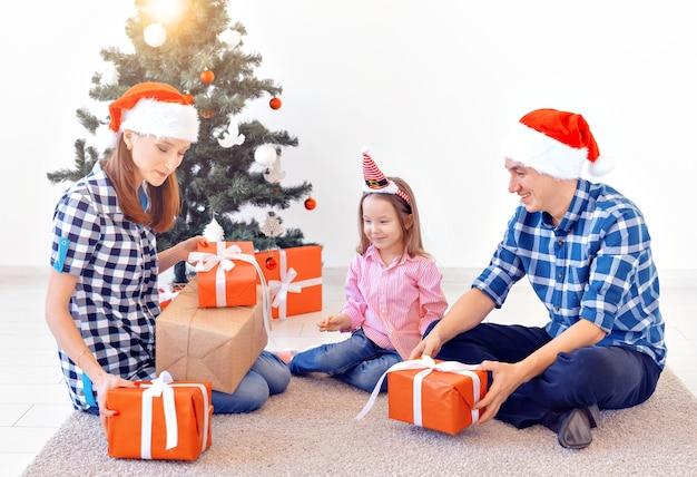 Conceito de natal e férias - família abrindo o presente de natal na frente da árvore.