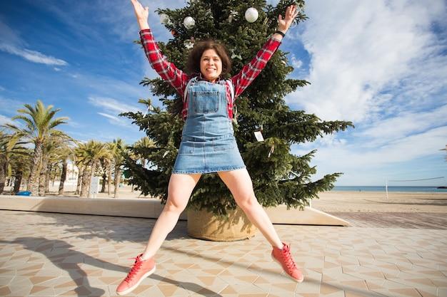 Conceito de natal e férias - mulher pulando feliz sobre a árvore de natal.