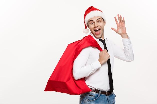 Conceito de natal - empresário bonito comemorar feliz natal e feliz ano novo usar chapéu de papai noel com saco grande vermelho de papai noel.