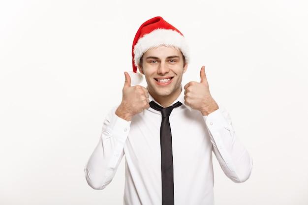 Conceito de natal - empresário bonito usar chapéu de papai noel aparecendo na parede branca isolada.