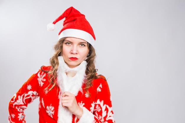 Conceito de natal, feriados e emoções - mulher malvada com raiva fantasiada de papai noel com barba postiça na parede branca com espaço de cópia
