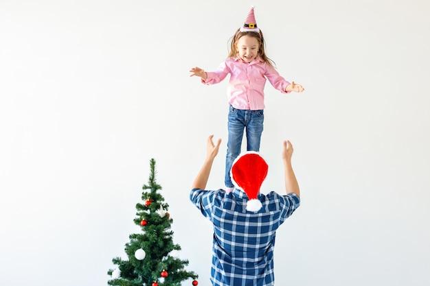Conceito de natal, feriados e paternidade - pai engraçado com chapéu de papai noel joga sua filha em um fundo branco com espaço de cópia.