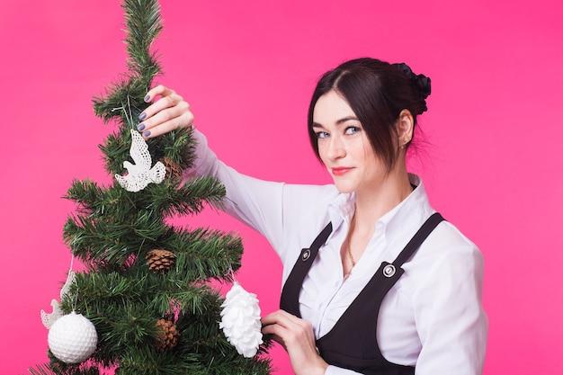Conceito de natal, feriados e pessoas - jovem mulher feliz decorando a árvore de natal na parede rosa.