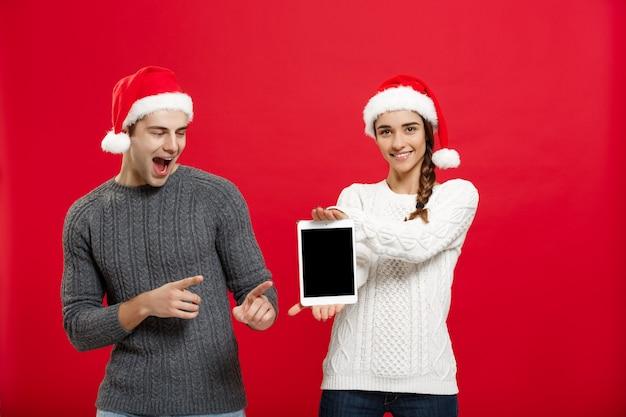 Conceito de natal - jovem casal feliz em suéteres de natal surpreendente algo no tablet digital.