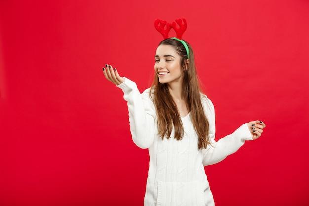 Conceito de natal - jovem senhora caucasiana atraente usa fita de cabelo de rena comemorando no dia de natal.