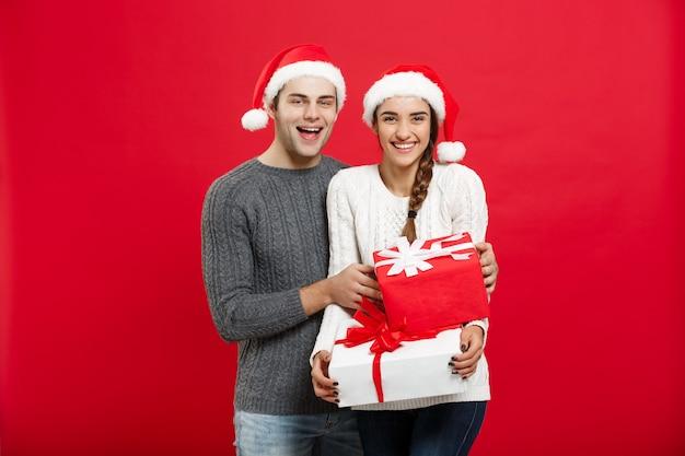 Conceito de natal - lindo namorado jovem com camisola de natal surpreende a namorada com presentes.