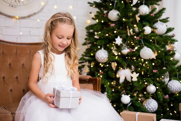 Conceito de natal - menina feliz com caixa de presente na sala de estar com árvore de natal