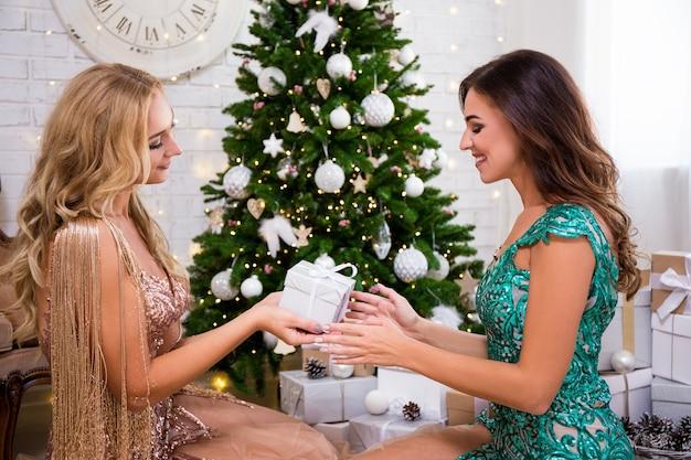 Conceito de natal - mulher com lindo vestido dando um presente para a amiga na sala de estar com árvore de natal decorada