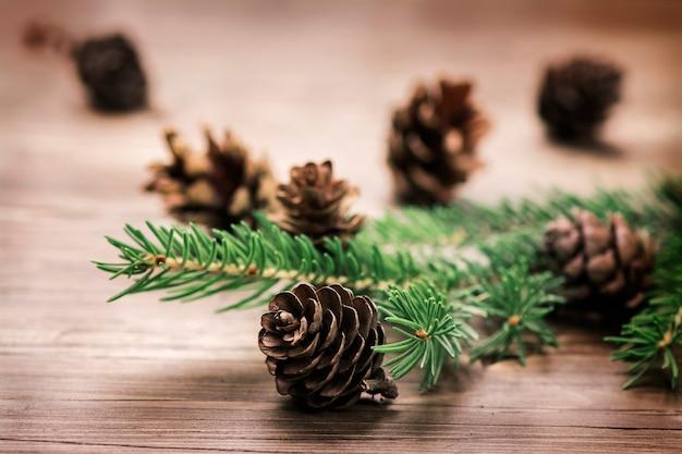 Conceito de natal: pinhas e ramos de abeto em fundo de madeira.