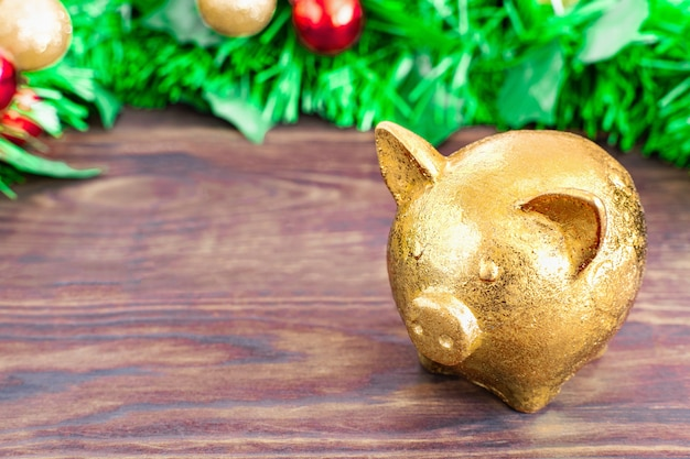 Conceito de natal - símbolo de ano porco dourado fica em uma mesa de madeira com fundo de galhos de árvores de natal