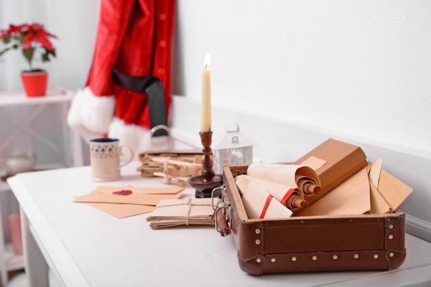 Conceito de natal. traje de papai noel pendurado na sala branca. baú com listas de desejos sobre a mesa, close-up