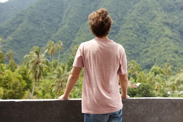 Conceito de natureza e liberdade. vista traseira do homem caucasiano turista olhando para floresta verde