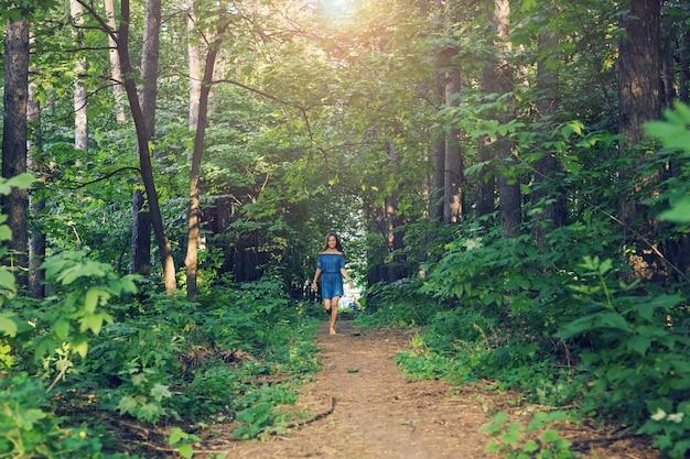 Conceito de natureza, pessoas e estilo de vida - mulher jovem e bonita em um vestido correndo na floresta de verão