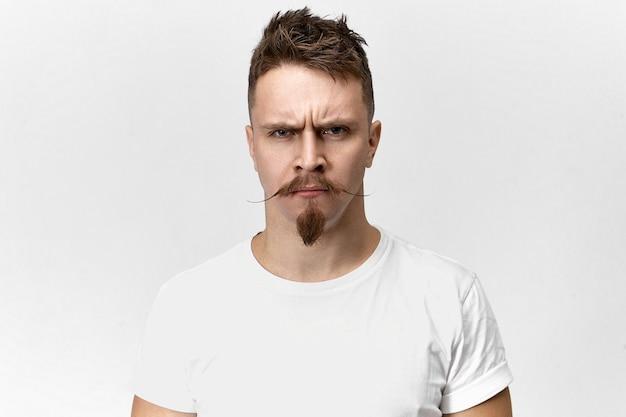 Conceito de negatividade, mau humor e emoções. retrato de homem barbudo ofendido mal-humorado com bigode engraçado hipster olhando para a câmera com olhar zangado, carrancudo, insatisfeito com um barulho irritante