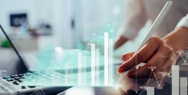 Conceito de negociação do mercado de ações, mão usando tablet e laptop com tela de gráfico de análise de show no escritório.