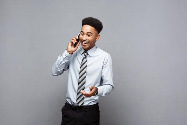 Conceito de negócio - alegre empresário africano americano profissional feliz falando no celular com o cliente.