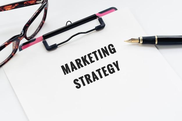 Conceito de negócio, área de transferência com a palavra estratégia de marketing, caneta e óculos em branco backgro