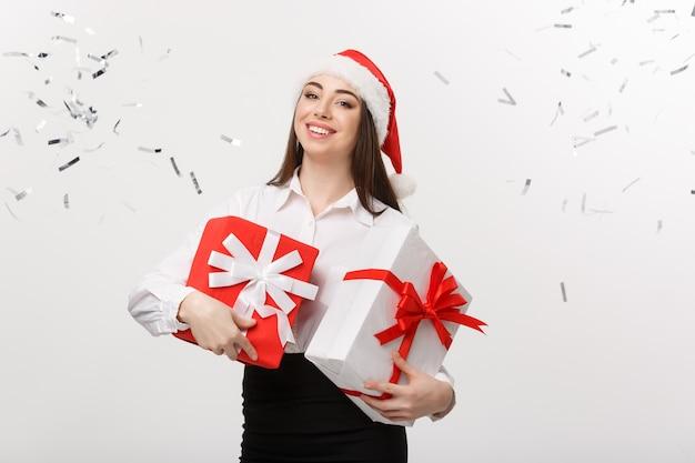 Conceito de negócio: bela jovem mulher de negócios caucasiana com chapéu de papai noel segurando uma caixa de presente e confete