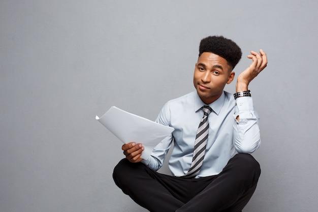 Conceito de negócio - bonito jovem profissional africano americano empresário leitura séria de documentos.