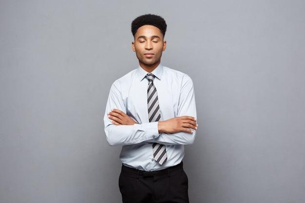 Conceito de negócio - braços confiantes do empresário afro-americano profissional feliz cruzados.