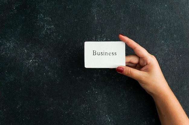 Conceito de negócio, cartão de visita com negócios escrito nas mulheres mão segurando