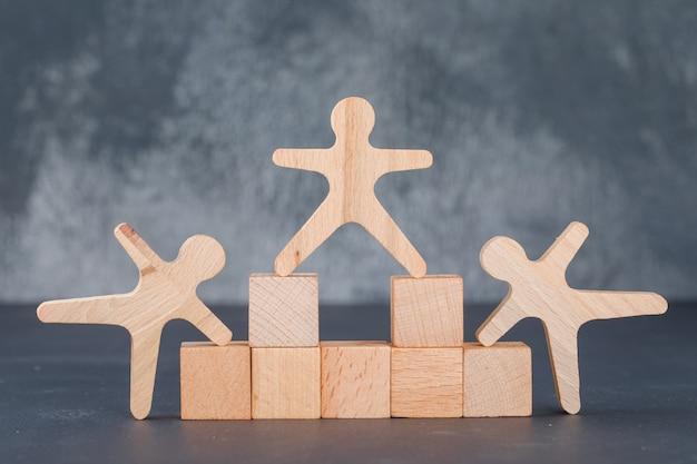 Conceito de negócio com blocos de madeira com figuras humanas de madeira.