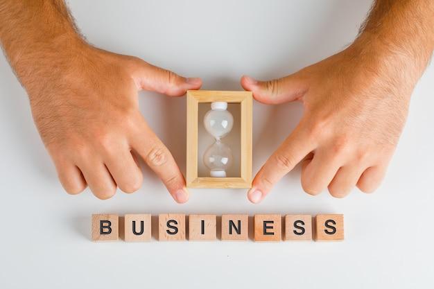 Conceito de negócio com blocos de madeira na mesa branca plana leigos. homem mãos segurando uma ampulheta.