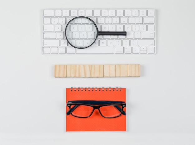 Conceito de negócio com blocos de madeira, óculos, lupa no teclado na configuração de plano de fundo branco.