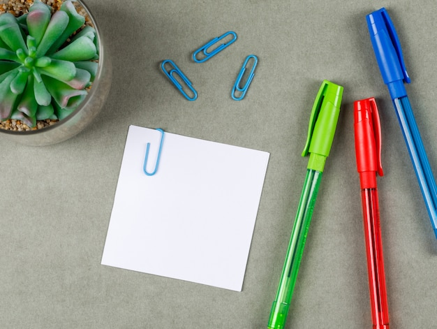 Conceito de negócio com canetas, clipes de papel, nota pegajosa, planta na superfície plana cinza leigos.