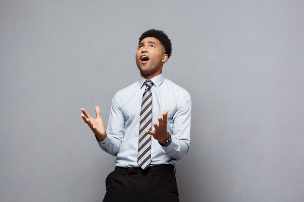 Conceito de negócio - confiante alegre jovem afro-americano, mostrando as mãos na frente dele com uma expressão decepcionada sobre a parede cinza.