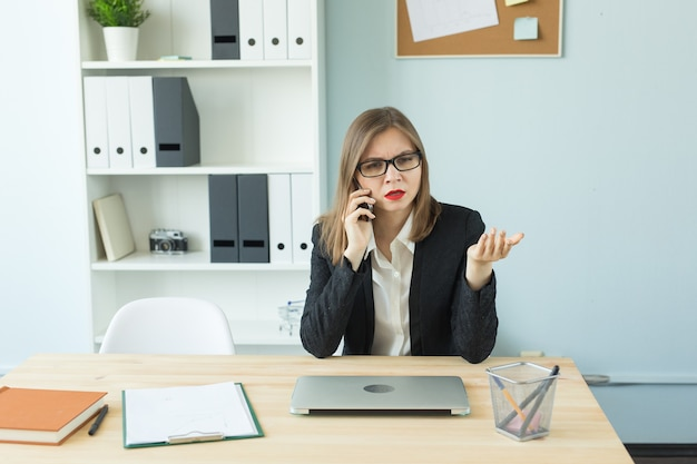 Conceito de negócio, corretor de imóveis e pessoas - mulher atraente no escritório, falando no telefone e fazer anotações.