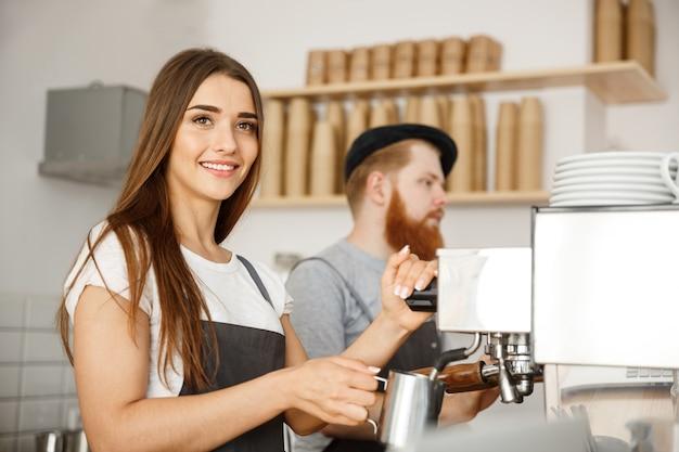 Conceito de negócio de café - retrato de senhora barista no avental preparando e cozinhando leite para café com seu parceiro enquanto está de pé no café.