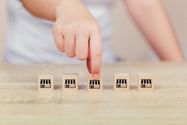 Conceito de negócio de franquia, mão de mulher escolher blog madeira com marketing de franquia.
