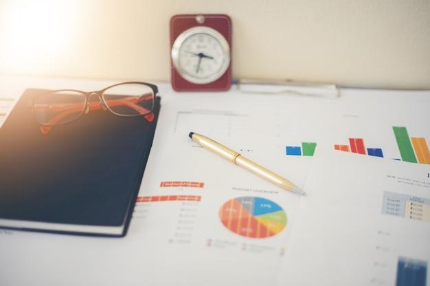 Conceito de negócio de gráficos de trabalho e análise de escritório e relógio na mesa