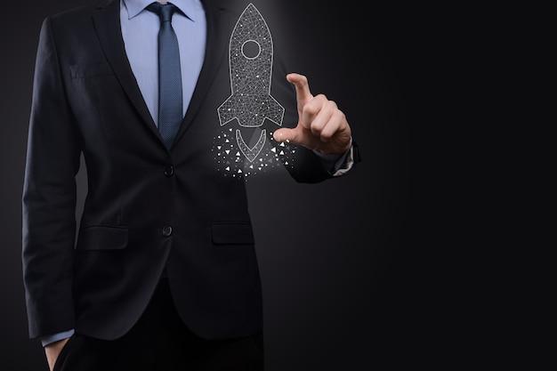 Conceito de negócio de inicialização, empresário segurando ícone de foguete transparente está lançando e voar para fora da tela com conexão de rede na superfície escura