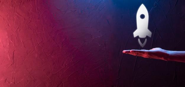 Conceito de negócio de inicialização, empresário segurando o tablet e ícone de foguete está lançando e voar para fora da tela com conexão de rede em fundo escuro.