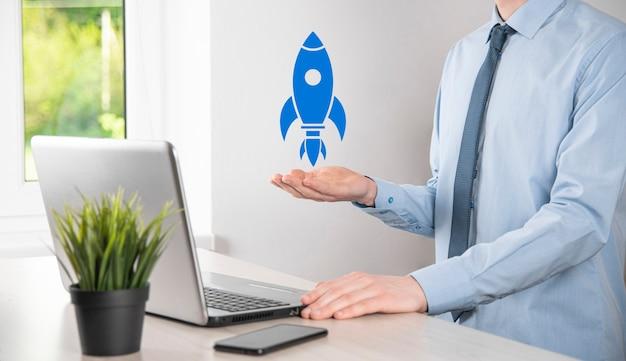 Conceito de negócio de inicialização, empresário segurando tablet e ícone de foguete está lançando e voar para fora da tela com conexão de rede em fundo escuro.