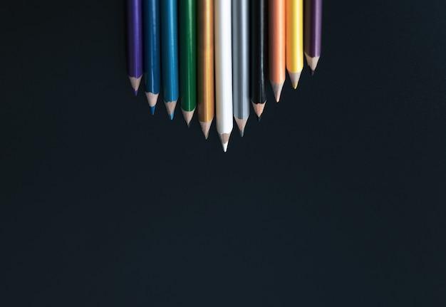 Conceito de negócio de liderança. lápis de cor branca levar outra cor em fundo preto