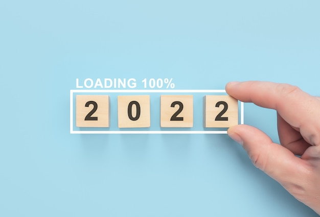 Conceito de negócio de planejamento de 2022 carregando novo ano 2022 com a mão colocando cubo de madeira na barra de progresso