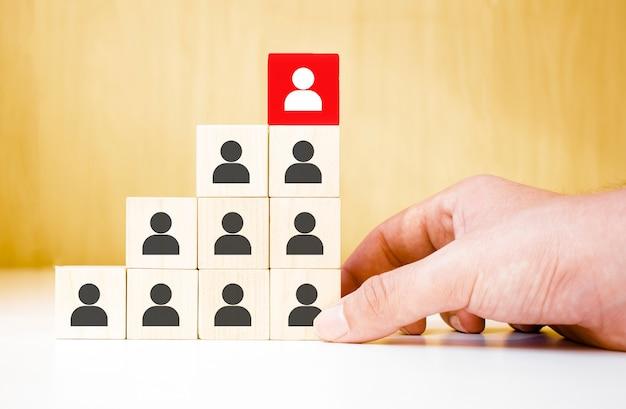 Conceito de negócio de recrutamento e gerenciamento de recursos humanos, mão colocando bloco de cubos de madeira no topo da pirâmide, espaço de cópia